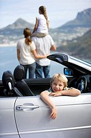 Family standing at roadside, looking at coastal scenery, focus on boy 6-8 sitting in convertible car, portrait