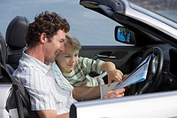 Father and son 6-8 sitting in convertible car, looking at road map, smiling, side view