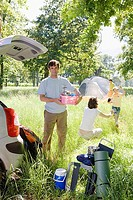 Family unloading car on camping trip, focus on man holding pink container beside car boot, smiling, portrait