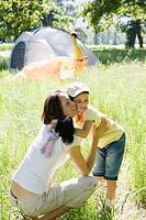 Mother and daughter 8-10 embracing on camping trip in rural setting, smiling, side view