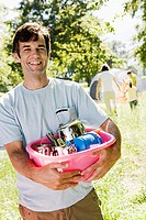 Family unloading car on camping trip, focus on man holding pink container, smiling, portrait