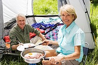 Senior woman serving husband fried breakfast on camping trip, man sitting inside tent, smiling, portrait