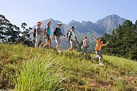 Multi-generational family hiking on mountain trail, walking in line, boy 8-10 leading, side view