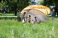Multi-generational family assembling orange tent on camping trip in woodland clearing, side view