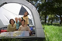 Multi-generational family relaxing inside tent in woodland clearing, smiling, portrait