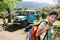 Group of young adults departing on hiking trip, man unloading jeep, focus on woman in foreground (thumbnail)