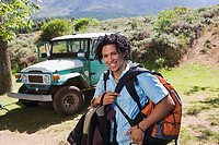 Young man unloading parked jeep at start of camping holiday, carrying rucksacks, smiling, portrait