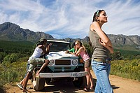 Four young adults leaning on jeep bonnet on dirt track in mountain valley, consulting map (thumbnail)