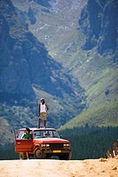 Young couple, in mid-distance, standing beside parked jeep on dirt track in mountain valley, woman on roof