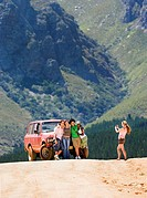 Young woman photographing four friends standing beside parked jeep on dirt track in mountain valley (thumbnail)