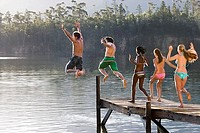 Five young adults, in swimwear, jumping side by side from jetty into lake, rear view