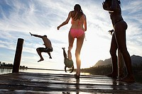 Four young adults, in swimwear, jumping from jetty into lake at sunset, rear view surface level