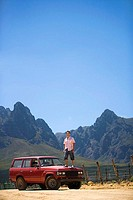 Young man standing on bonnet of parked red SUV on dirt track in mountain valley, looking at scenery