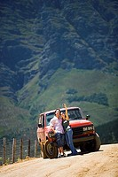 Young couple standing in front of parked red SUV on dirt track in mountain valley, woman taking self-portrait with camera