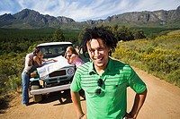 Four young adults consulting map beside jeep on dirt track in mountain valley, focus on man, smiling, portrait