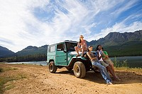 Four young adults leaning against bonnet of parked jeep on dirt track beside lake, looking at scenery