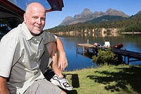 Mature man sitting in boot of parked SUV, smiling, side view, portrait, lake and jetty in background
