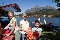 Girl 8-10 unloading life jackets from SUV with mother and grandmother, rest of family on lake jetty beside boat