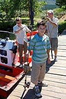 Boy 8-10 standing on lake jetty with fishing rod, father and grandfather loading motorboat in background
