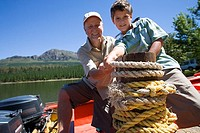 Grandfather and grandson 8-10 standing in motorboat beside lake jetty, tying rope to mooring post