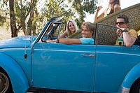 Four teenagers 17-19 sitting in blue convertible car with surfboard, portrait, side view