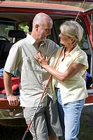 Senior couple standing beside parked SUV, arms around each other, man with fishing rod, smiling