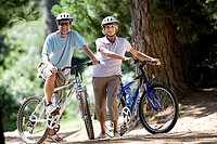 Senior couple, in cycling helmets, mountain biking on woodland trail, smiling, portrait