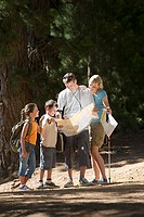 Family hiking on woodland trail, consulting map, smiling