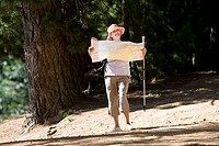 Senior woman hiking on woodland trail, carrying hiking pole and consulting map, smiling, front view