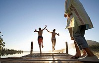 Multi-generational family on jetty at sunset, children 7-10 jumping into lake, rear view surface level, backlit, lens flare