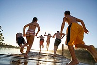 Six family members, in swimwear, jumping from jetty into lake at sunset, rear view lens flare, backlit, surface level, tilt