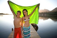 Teenage boy and girl 12-14 standing on lake jetty at sunset, holding aloft green towel, smiling, portrait