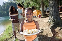 Family having lunch on camping trip beside lake, focus on girl 7-9 with plate of corncobs, smiling, portrait