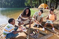 Family cooking food on camping trip beside lake, smiling, portrait