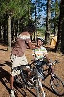 Father and son 8-10 mountain biking on camping trip, man adjusting boy¥+++§¥s cycling helmet strap