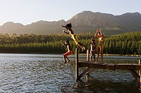 Family, in swimwear, standing on jetty, father and son 8-10 jumping into lake, side view
