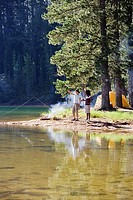 Couple, in mid-distance, fishing near lakeside campfire, woman holding aloft fish, side view