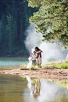 Father and son 8-10, in mid-distance, fishing near lakeside campfire, man holding catch, boy with fishing rod