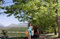 Woman unloading provisions from parked SUV on lakeside camping trip, carrying picnic hamper, smiling, portrait