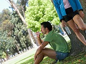 Couple taking break from jogging in park, man drinking bottle of water beside tree, woman leaning against trunk tilt