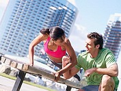 Couple exercising in park, woman doing press-ups on bench, man offering encouragement, smiling tilt