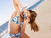 Girl 10-12, in bikini, standing on sandy beach, taking photograph with digital camera, tilting head, portrait tilt