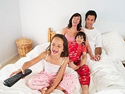 Family sitting on double bed at home, watching television, girl 5-7 using remote control, laughing