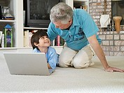 Senior man and grandson 5-7 using laptop on living room floor, smiling
