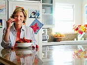 Woman sitting at breakfast table in kitchen, eating fresh bowl of strawberries, smiling, portrait