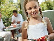 Parents sitting at balcony table, focus on girl 6-8 holding bowl of strawberries in foreground, smiling, portrait