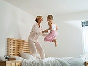 Mother and daughter 6-8 jumping up and down on double bed at home, laughing, side view
