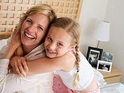 Mother and daughter 6-8 sitting on double bed at home, girl embracing woman, smiling, close-up, portrait tilt