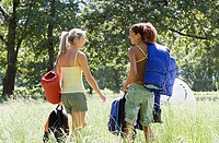 Two young women, with rucksacks and sleeping bags, departing on hiking trip in woodland clearing, rear view