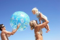 Young family playing on beach, father holding beach ball, mother lifting daughter 2-3 above head